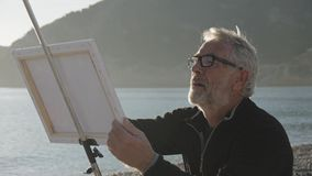 Старший человек красит изображение на пляже Средняя съемка пожилого мужского художника крася пляж холста на море на заходе солнца сток-видео
