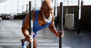 Старший человек нажимая скелетон веса в студии 4k фитнеса сток-видео