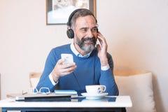 Старший человек наслаждаясь его любимой музыкой Стоковые Изображения