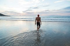 Старший человек подготавливая поплавать в море на зоре стоковые изображения
