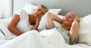 Старший человек покрывая его уши пока женщина храпя в спальне видеоматериал