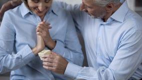 Старший человек представляя подарок к счастливой удивленной жене, празднуя годовщину стоковое изображение