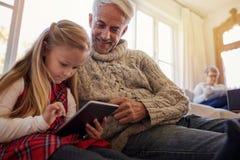 Старший человек при внучка используя цифровую таблетку дома Стоковые Фото