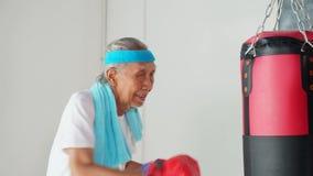 Старший человек пробивая мешок бокса