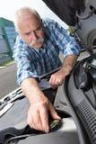 Старший человек проверяя уровень воды двигателя на автомобиле Стоковые Изображения RF