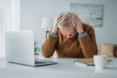 Старший человек работая в офисе и страдая стоковое изображение rf
