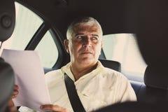 Старший человек работая в такси стоковое фото