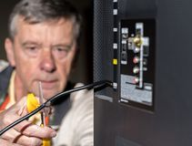 Старший человек режа шнур на его пакете кабельного телевидения стоковые изображения