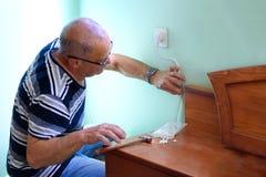 Старший человек ремонтируя в комнате стоковое изображение rf