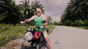 Старший человек сидя на мотоцикле и начиная двигатель на тропическом ландшафте пальм Пожилой мотоциклист человека дальше видеоматериал