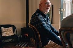 Старший человек сидя на стуле дома и говорить стоковые изображения