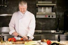 Старший человек с бородой в белой форме режет овощи в кухне стоковая фотография rf