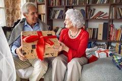 Старший человек с настоящими моментами тратя рождество вместе с женщиной стоковое изображение