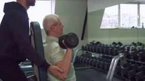 Старший человек тренирует его плеча стоковое изображение