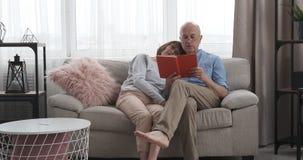Старший человек читая книгу к его жене дома видеоматериал