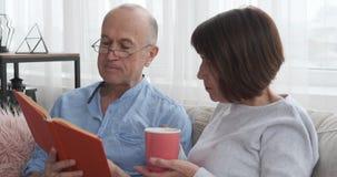 Старший человек читая книгу к его кофе жены выпивая видеоматериал