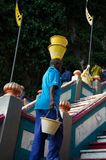 Старший чернокожий человек с ведрами на его голове и руке вверх по лестницам Стоковая Фотография