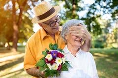 Старший человек давая букет покрашенных цветков к его жене Стоковая Фотография