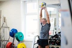 Старший человек в спортзале разрабатывая используя kettlebells Стоковое Изображение RF