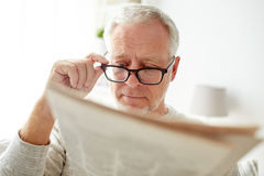 Старший человек в стеклах читая газету дома Стоковое Фото
