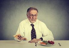 Старший человек есть салат свежего овоща избегая наварной пиццы Концепция выборов питания здорового питания стоковое изображение