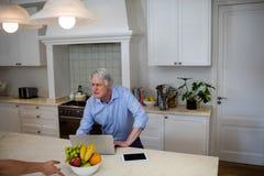 Старший человек используя взаимодействовать пока использующ компьтер-книжку в кухне стоковая фотография rf