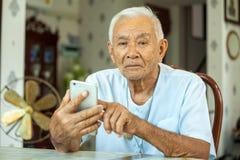 Старший человек используя мобильный телефон дома Стоковая Фотография RF