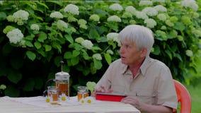 Старший человек используя цифровую таблетку в таблице сада лета с чаем видеоматериал