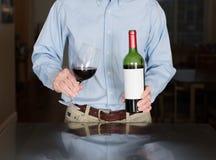 Старший человек лить от бутылки вина с пустым ярлыком Стоковое фото RF