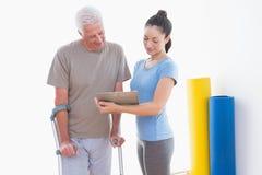 Старший человек и его тренер смотря доску сзажимом для бумаги Стоковая Фотография