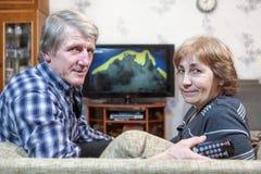 Старший человек и женщина сидя перед ТВ поворачивая назад на кресле Стоковые Изображения RF