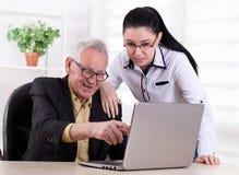 Старший человек и молодая женщина смотря компьтер-книжку Стоковые Фотографии RF