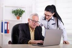 Старший человек и молодая женщина смотря компьтер-книжку Стоковые Фото