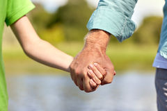 Старший человек и ребенок держа руки Стоковая Фотография