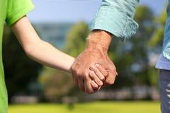 Старший человек и ребенок держа руки Стоковое Изображение