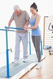 Старший человек идя с параллельными брусьями и тренер помогают Стоковая Фотография RF