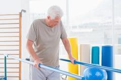 Старший человек идя с параллельными брусьями Стоковая Фотография