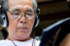 Старший человек наслаждаясь музыкой стоковое фото