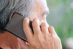Старший человек наслаждаясь на его телефоне Стоковые Изображения