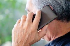 Старший человек наслаждаясь на его телефоне Стоковое Изображение RF