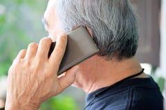Старший человек наслаждаясь на его телефоне стоковые фотографии rf