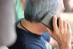 Старший человек наслаждаясь на его телефоне Стоковые Фото
