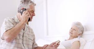 Старший человек на телефонном звонке держа пилюльки сток-видео