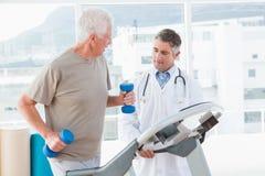 Старший человек на третбане с терапевтом Стоковые Фото