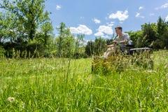 Старший человек на zero травокосилке поворота в луге Стоковые Изображения RF