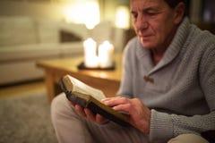 Старший человек дома читая библию, горящие свечи за им Стоковые Фотографии RF