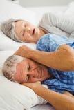 Старший человек покрывая ее уши пока женщина храпя Стоковая Фотография RF