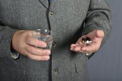 Старший человек принимая медицину с стеклом воды Стоковые Фотографии RF