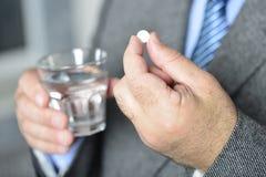 Старший человек принимая медицину с стеклом воды Стоковое Изображение RF