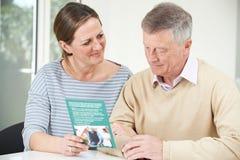 Старший человек при взрослая дочь смотря брошюру для Retiremen стоковые фотографии rf